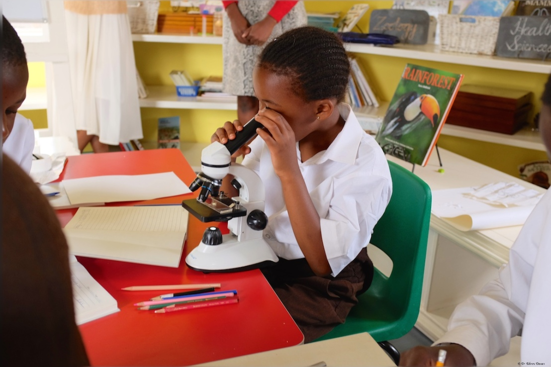 A six year old using the microscope for the first time